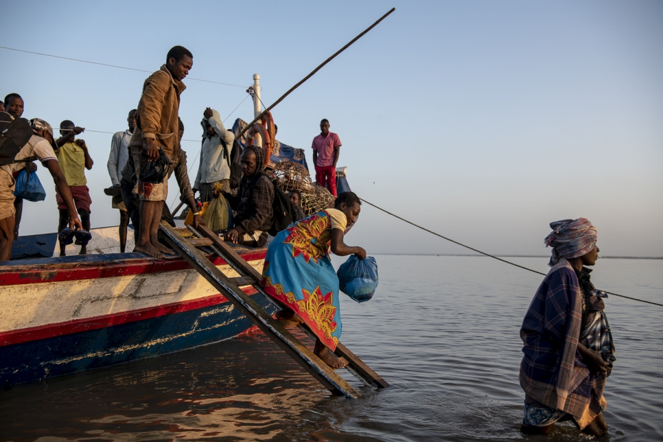 People displaced by Cyclone Idai disembark a boat at dawn in the port of Beira. Finding their homes destroyed, and belongings gone, many people have fled to Beira to seek international assistance.