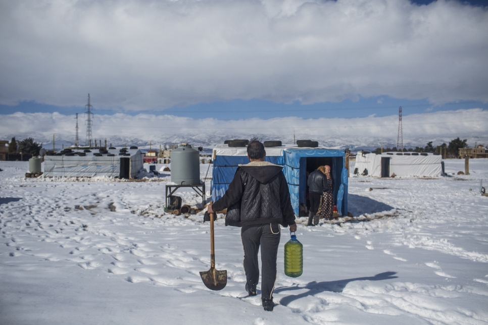 A Syrian refugee walks through the snow with a shovel and gasoline at the informal settlement camp of Douress. Lebanon is currently experiencing its harshest winter in years
