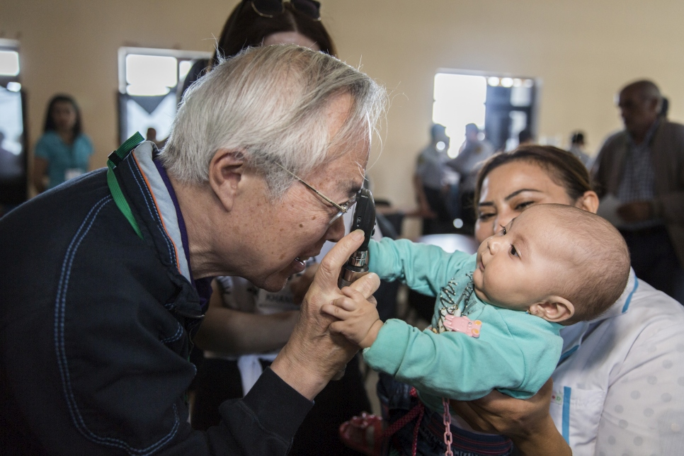 Dr Akio Kanai tries to examine an internally displaced infant's eyes.  During a six day eye-testing trip, the team screened 2,882 people and distributed 2,433 pairs of eyeglasses. in addition, 141 pairs of eyeglasses are to be sent from Japan.