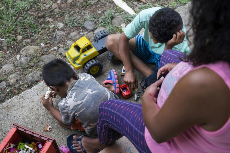 Andrea, a pregnant asylum-seeker from Nicaragua, sits with her two children as they play outside their new home in Costa Rica.