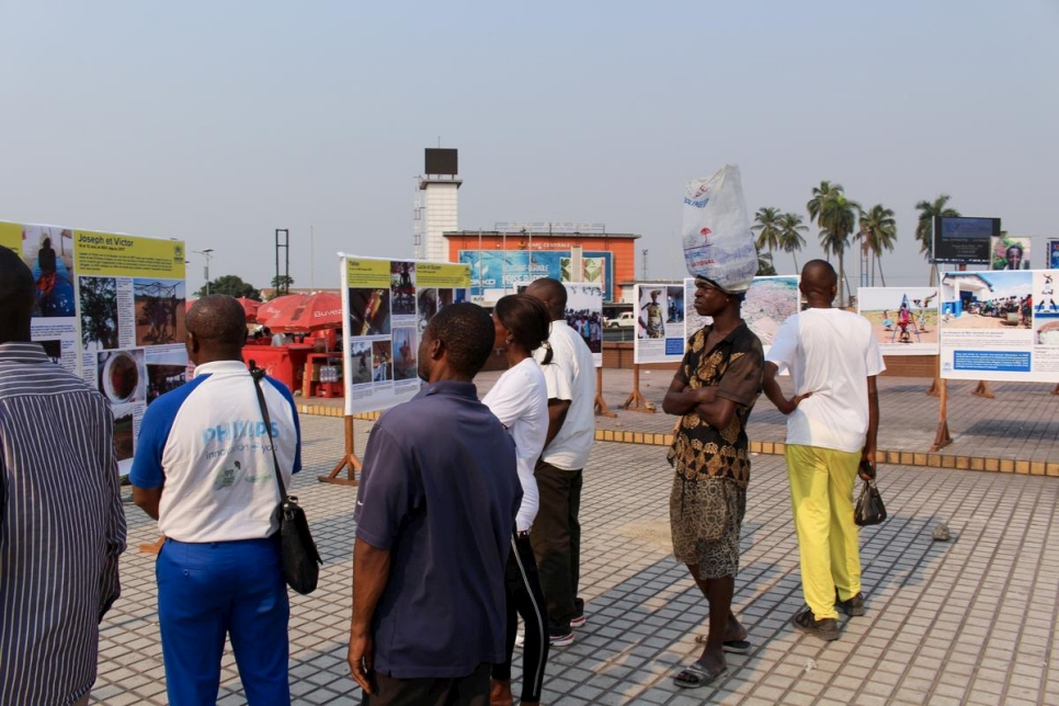 A group gathers at the outdoor photography exhibition to mark World Refugee Day in downtown Kinshasa, DRC.