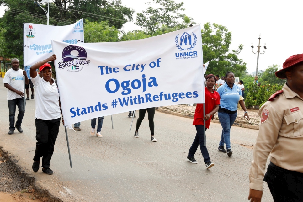 Residents of Ogoja in Nigeria's Cross River State take part in a \X68StepWithRefugees walk to commemorate World Refugee Day.