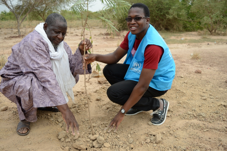 A Malian refugee and a UNHCR staffer plant a tree together to mark World Refugee Day in Goudoubo camp, Burkina Faso.