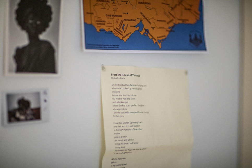 Postcards, poetry and a polaroid decorate wall where Bigoa Chuoi works. The poet's family fled Sudan's conflict and she was resettled as a refugee in Australia.