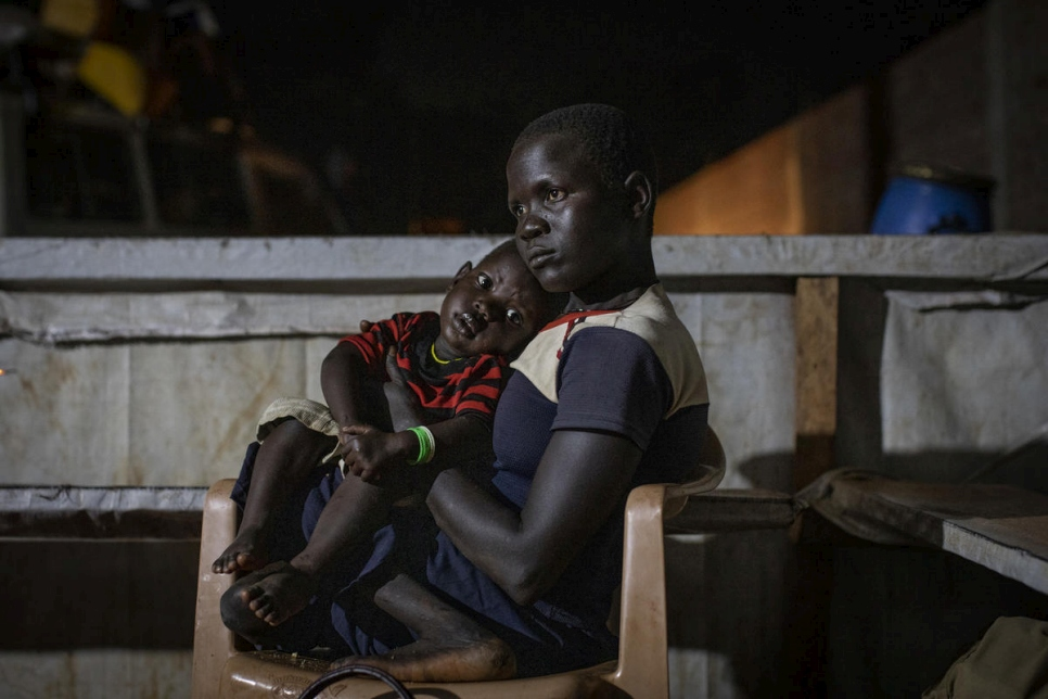 Democratic Republic of Congo. A newly arrived South Sudanese refugees mother holds her baby boy as they wait to receive a meal and accommodation at the transit centre in Aru