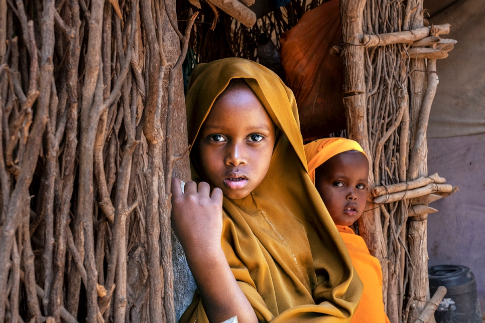 Five-year-old Somali refugee Filsan looks out from her home in Dadaab, Kenya, with her three-year-old sister Sundus. The siblings were born in Ifo refugee camp and the elder has ambitions she is already trying to fulfil through school.