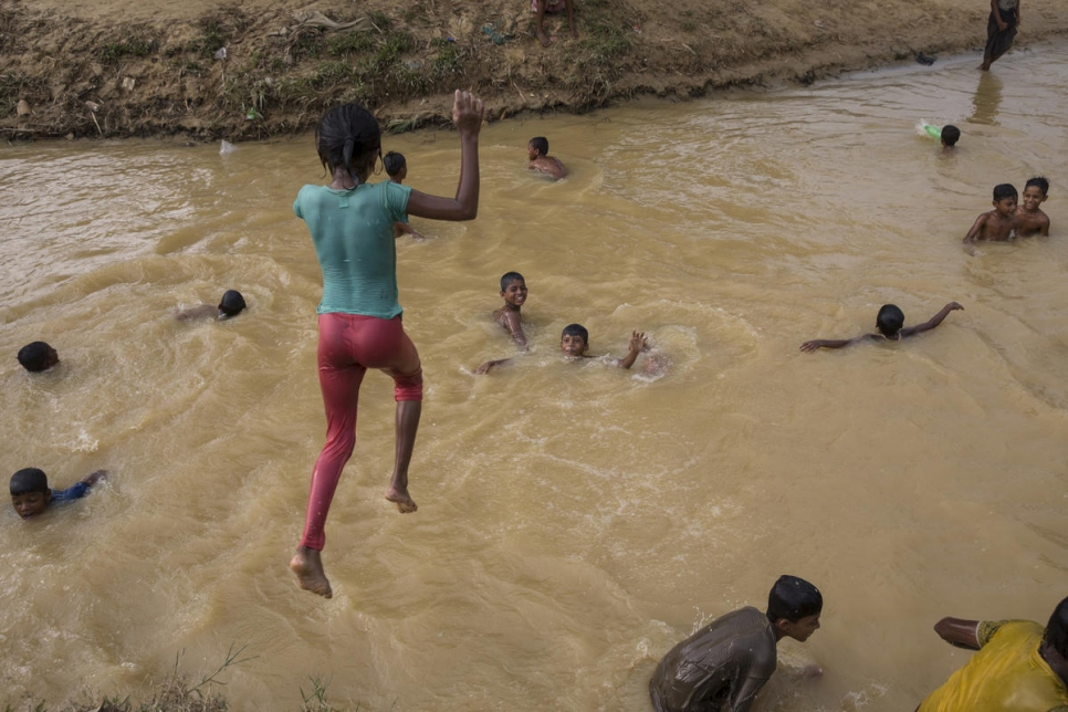 A child jumps into a muddy stream, after heavy rains at Balukhali refugee camp.