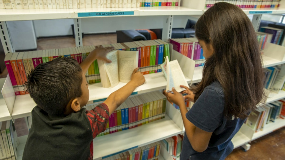 Samuel* and Maité* are checking the books inside the Biblioparque's library