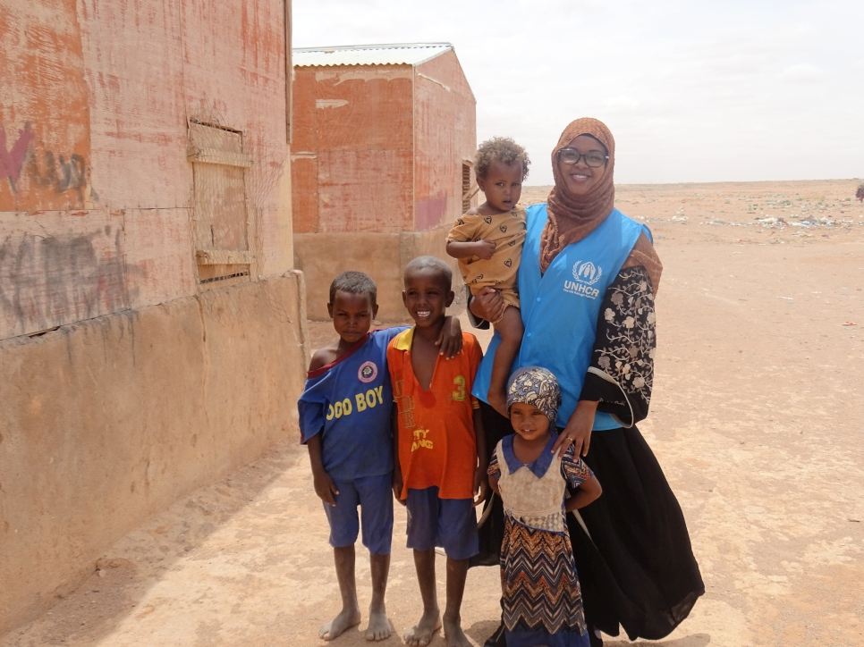 Bisharo Hussein (left) poses with young children in Galkacyo, Somalia where she works as a Protection Associate.