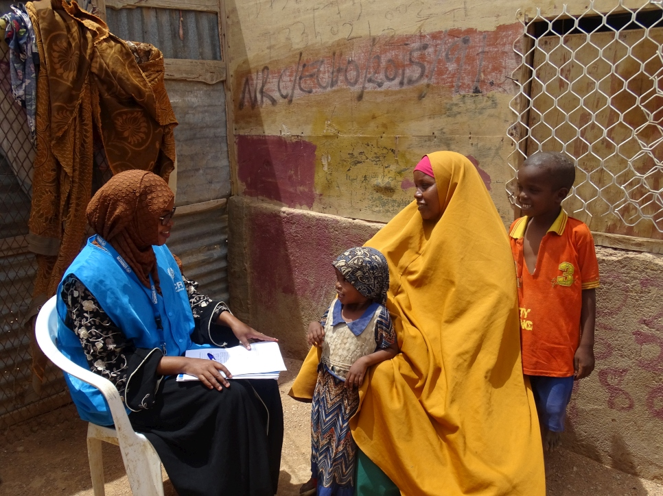 Bisharo (left) visits a family in Galkacyo, Somalia where she works as a Protection Associate.