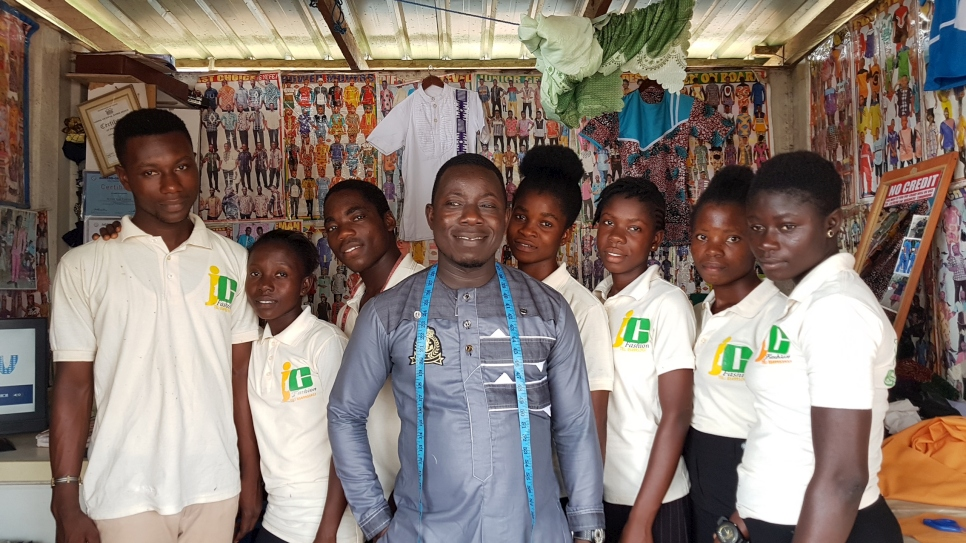 Ivorian refugee Bouhe Jean Claude poses with his staff in his tailoring shop in central Ghana.