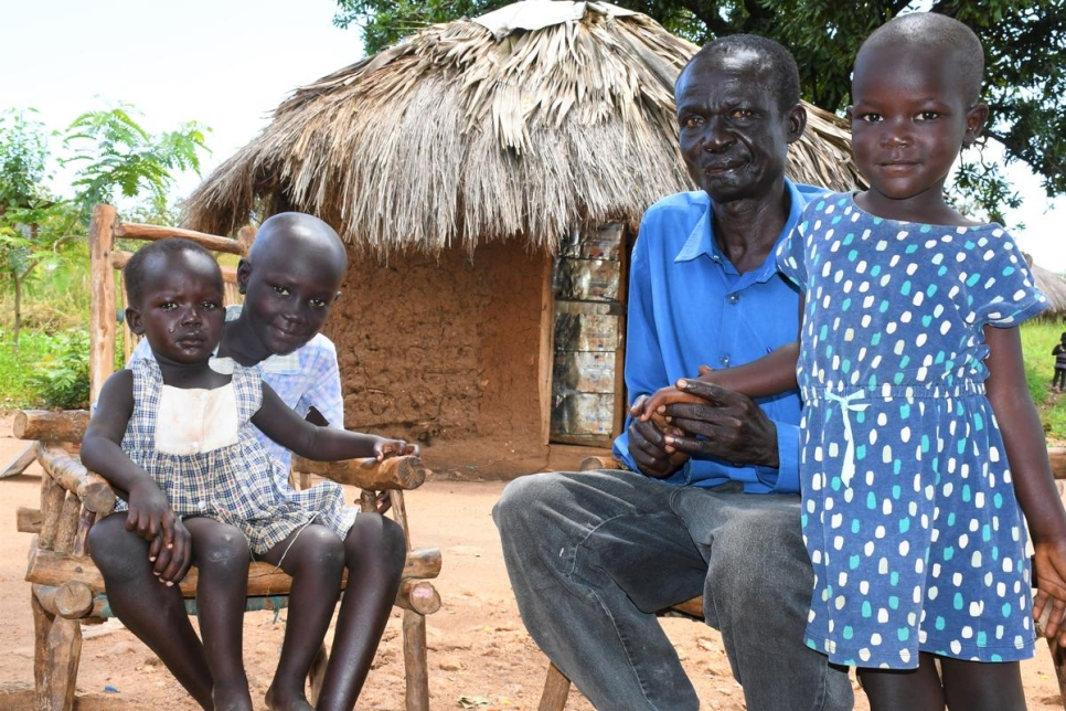 Rufas Taban sits with his three children (from left) Maria, Joseph and Blessing outside his shelter in Imvepi settlement, Uganda.