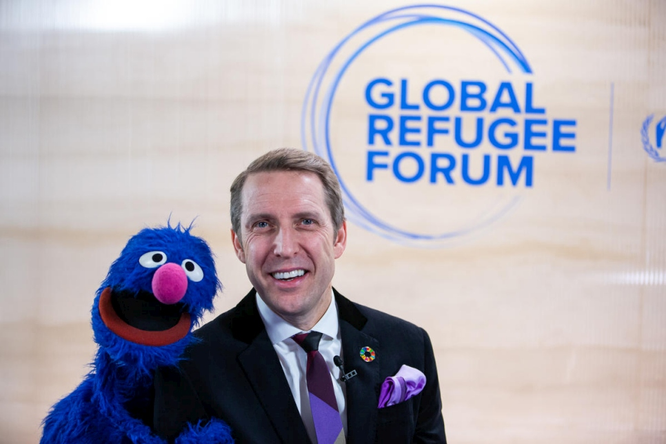 "John Goodwin, CEO of the LEGO Foundation, shares a joke with the Sesame Street muppet Grover. Grover has been conducting interviews at the Global Refugee Forum to be broadcast during the ""Sesame Street News"" segment of the children's television programme."