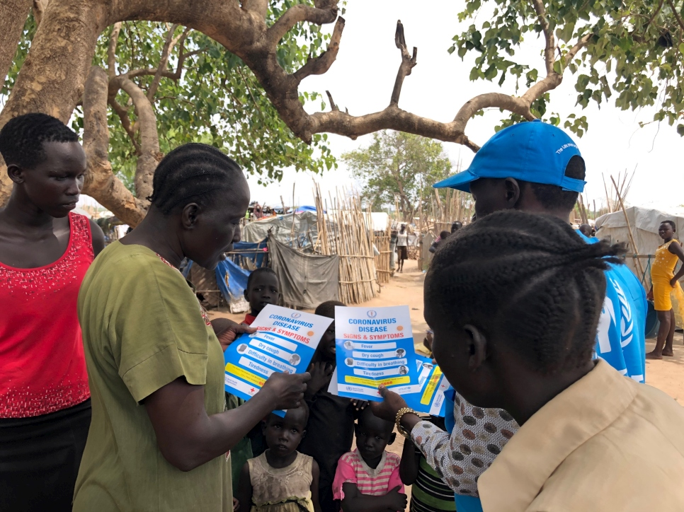 A group of internally displaced people read information on Coronavirus in Don Bosco IDP site near Juba, South Sudan.