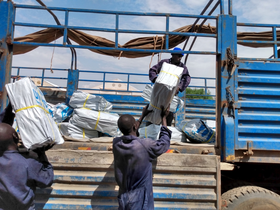 Loaders unpack bags of plastic sheets to be distributed as part of UNHCR's COVID-19 response in Juba, South Sudan.