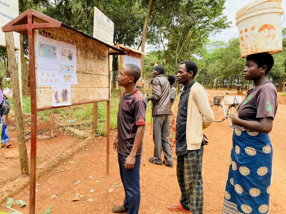 A group of refugees read information on the coronavirus at a distribution centre in Nduta camp, Tanzania.