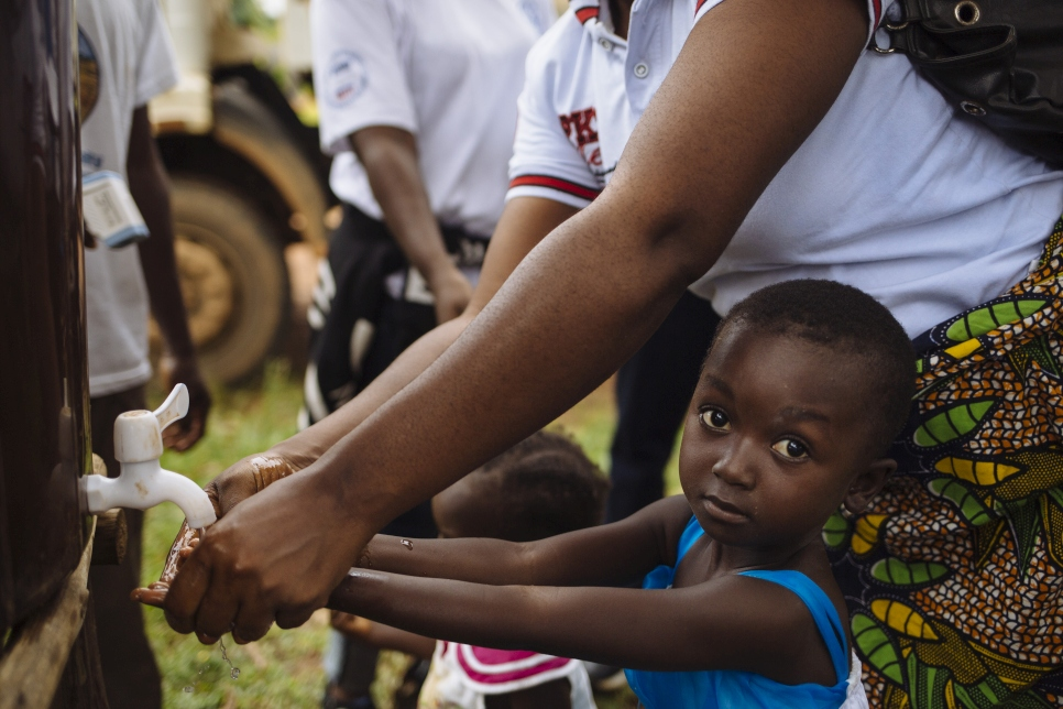 A young girl is helped by her mother to wash her hands as they and other refugees queue to have their temperature recorded in an effort to combat the transmission of the Ebola Virus Disease, at a border post near the Cavalla River, which demarcates the border with Côte d'Ivoire, in Maryland, Liberia.