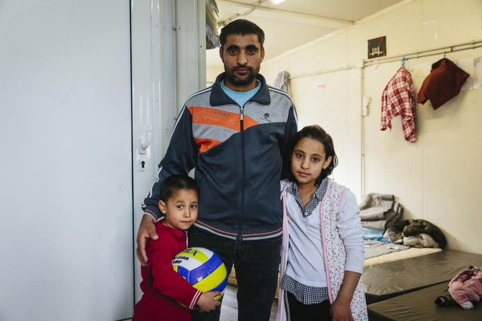 An Afghan asylum-seeker stands with two of his children at a reception centre in Fylakio, Greece, in February 2020.