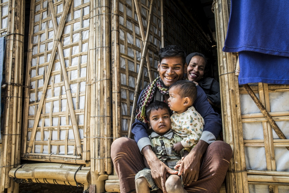 Twenty-seven-year-old Rohingya refugee, Abul Kalam, holds his 17-month-old baby Arafat and three-year-old son Ayaz in the doorway of the new monsoon-ready shelter
