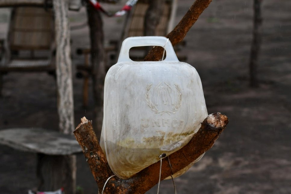A jerrycan filled with water is secured on a tree trunk in Ferida's compound in Bele settlement, Democratic Republic of the Congo.