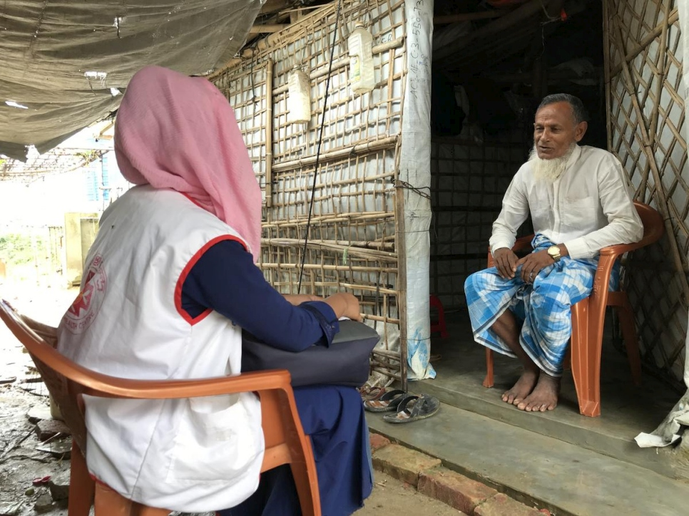 A Rohingya refugee trained as a community health worker visits a household in her community to raise awareness about COVID-19.