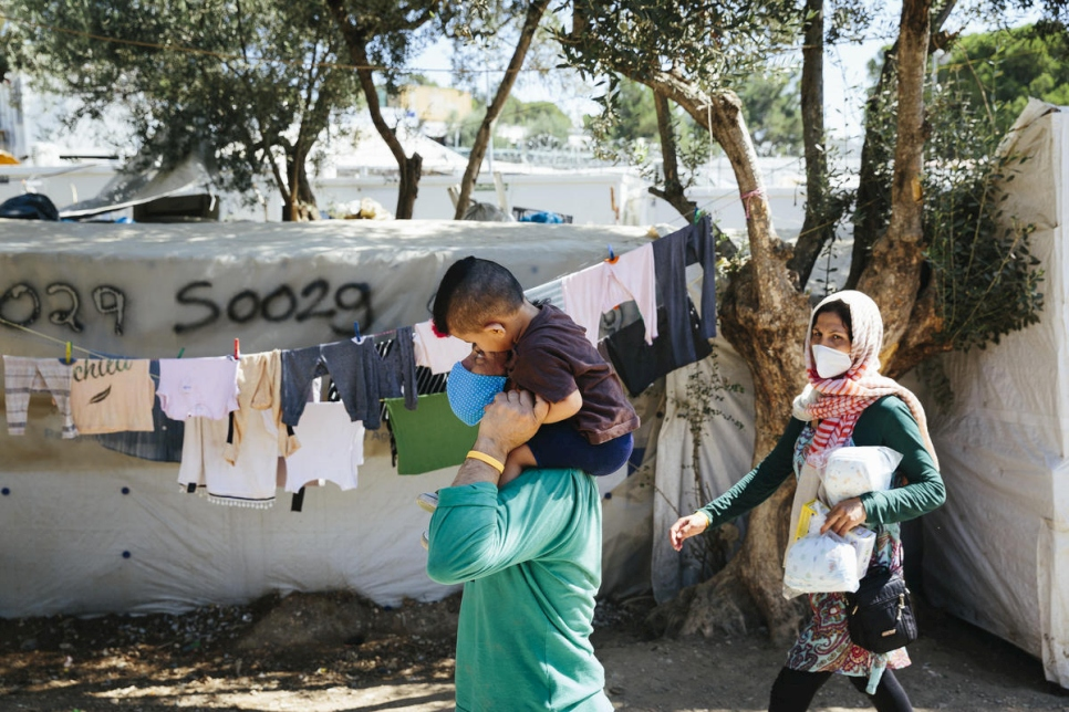 An Aghan refugee family walks through an informal camp outside the Moria Reception and Identification centre on the island of Lesbos, September 1, 2020.