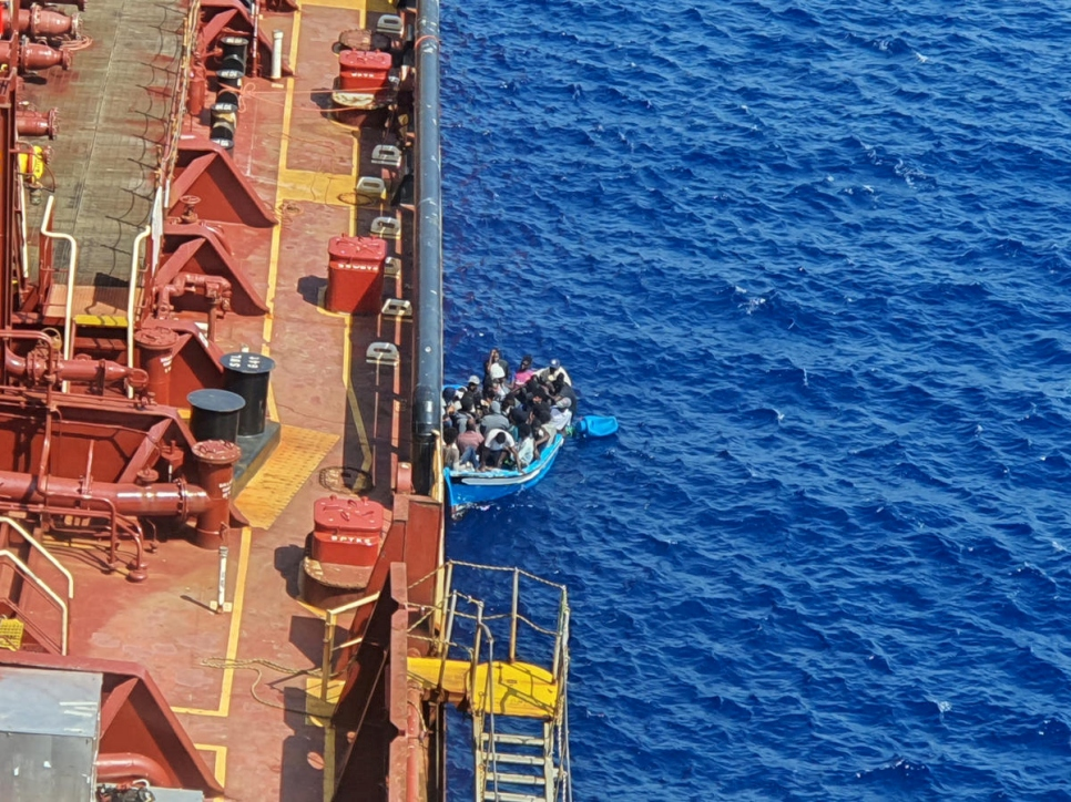 Malta. Migrants sit in a boat alongside the Maersk Etienne tanker