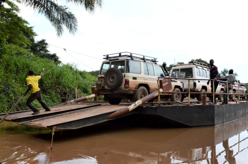 UNHCR vehicles cross the Ouaka river, a tributary of the Ubangui river, on a rickety ferry. They carry supplies for refugees from Democratic Republic of Congo to Toko Kota village.