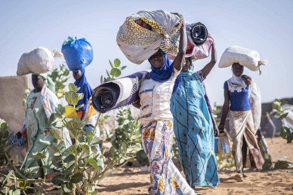 Malian refugee women carrying their belongings through Mbera refugee camp in Mali. Mbera camp in south-east Mauritania is home to nearly 60,000 Malian refugees.