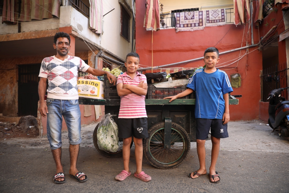 Syrian refugee, Gaith (in blue), 13, stands beside his father's fruit and vegetable cart in Beirut with his dad Samer Mohammed Ameno, 42, and brother Mohammed, 12. Gaith dreams of becoming a famous footballer and is ecstatic about moving to the city of his dream club, Real Madrid.