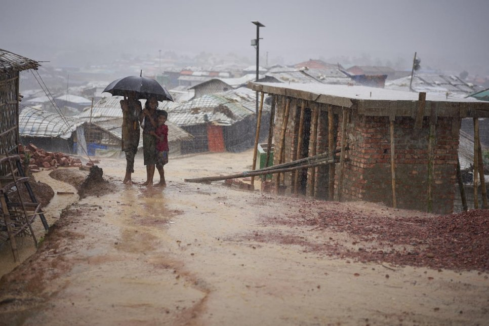 Bangladesh. Rohingya refugees walk through a heavy monsoon downpour