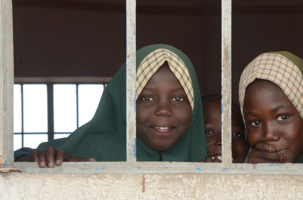 Displaced Nigerian girls peep through the window of their class at one of four schools established by Nansen Refugee Award Laureate, Zannah Mustapha in Borno State, Nigeria.