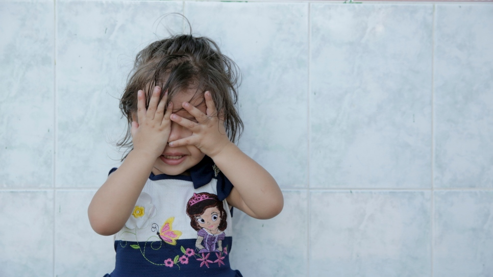 A young girl cover her eyes with her hands