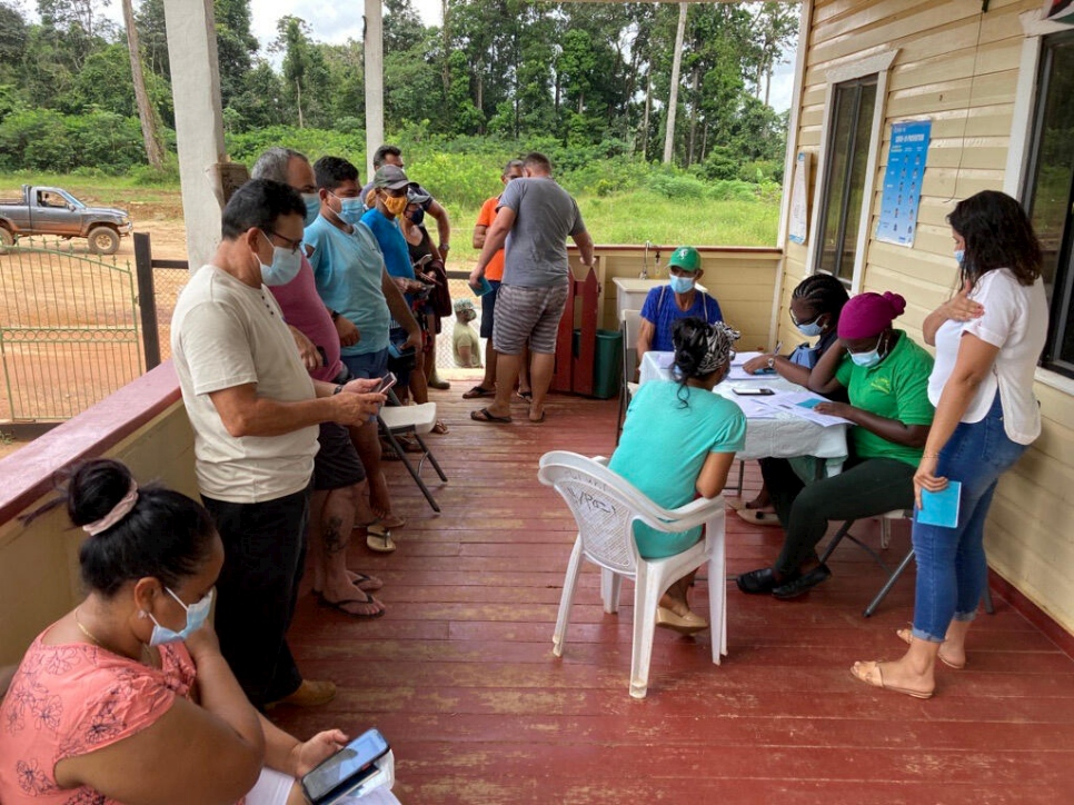 In Guyana, displaced people and locals line up to receive the COVID-19 jab.
