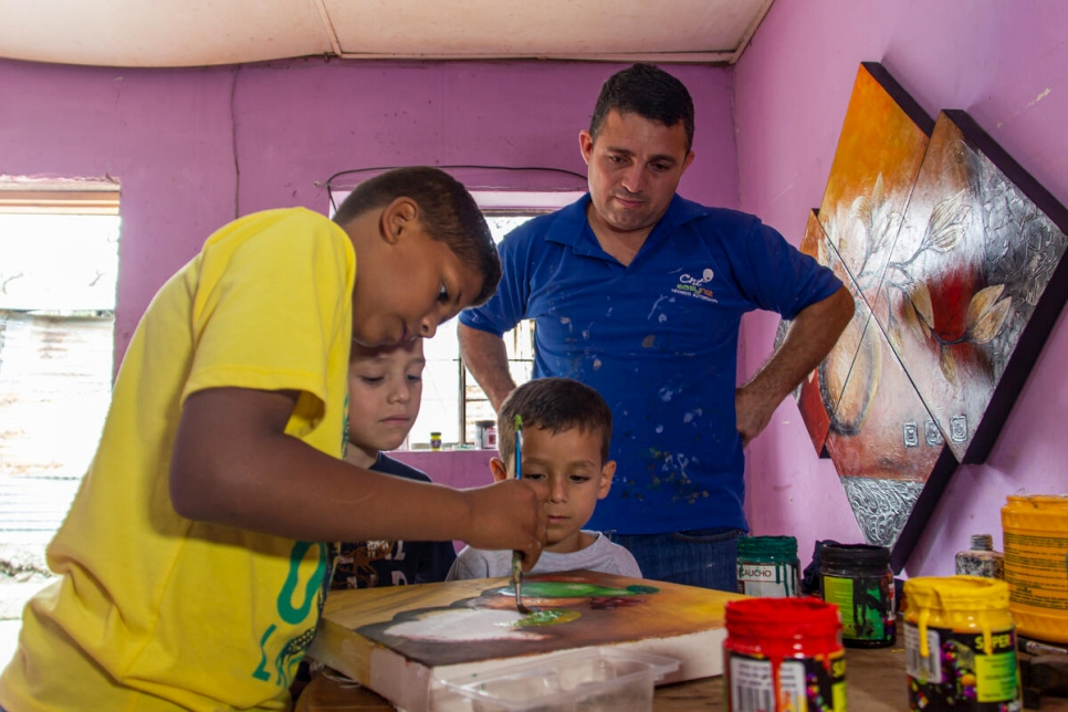José Soto supervises while his oldest son paints one of the canvases the family sell to earn an income.