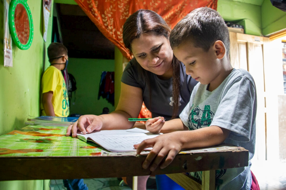 María José Mercado helps one of her sons with his homework. Getting regular status will help her children complete their education in Ecuador.
