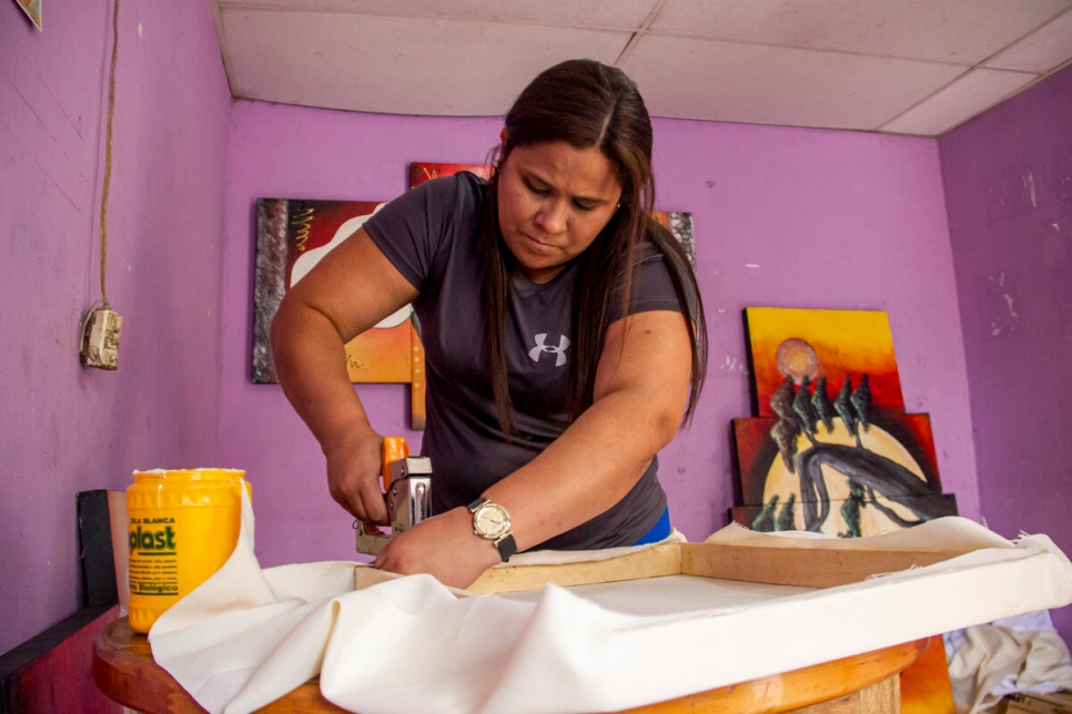 María José Mercado stretches one of the canvases that her husband will paint.