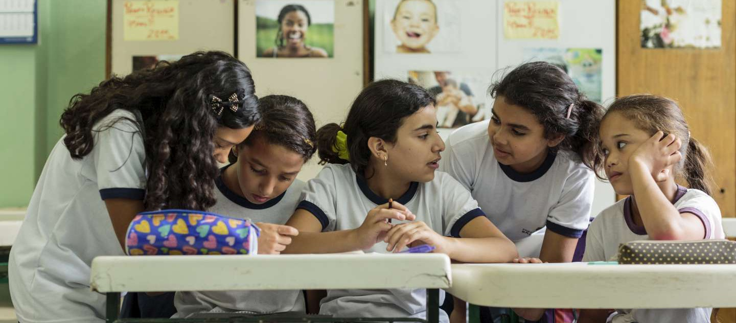 Syrian refugee Hanan Dacka (3rd from left), 12 years-old, confers with newly-made Brazilian friends (left to right) Anne Pinheiros de Souza, 12, Andressa Rabasco, 12, Julia Vanderlei, 12, and Maria Luiza de Sousa, 12, during classes at the Duque de Caxias Municipal School, in the Glicerio neighborhood of downtown Sao Paulo, Brazil, on February 25, 2016. Hanan arrived in Sao Paulo with her mother, Yusra Bakri, in early 2015 and was recognized as a refugee by the Brazilian government on September of that year. After only 4 days in a new classroom, she has started to make new friends, all of which already used to study alongside immigrants and refugees. Glicério, the school's neighborhood in the center of Sao Paulo, is the region to where the majority of immigrants and asylum seekers go to live as soon as they arrive in the city. Many children of those newly-arrived go to Duque de Caxias for elementary studies.