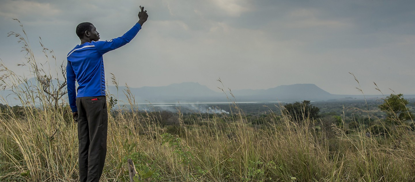 A young South Sudanese man tries to get signal on his mobile phone in Nyumanzi refugee settlement, Adjumani, northern Uganda. From this hill overlooking the refugee settlements, refugees can sometimes pick up the South Sudanese phone network and make cheaper calls home.