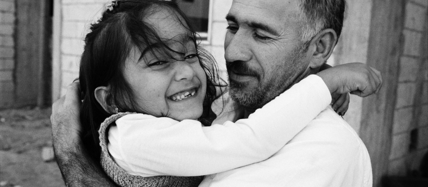 Aya hugs her father as they prepare to be resettled from Lebanon to France.