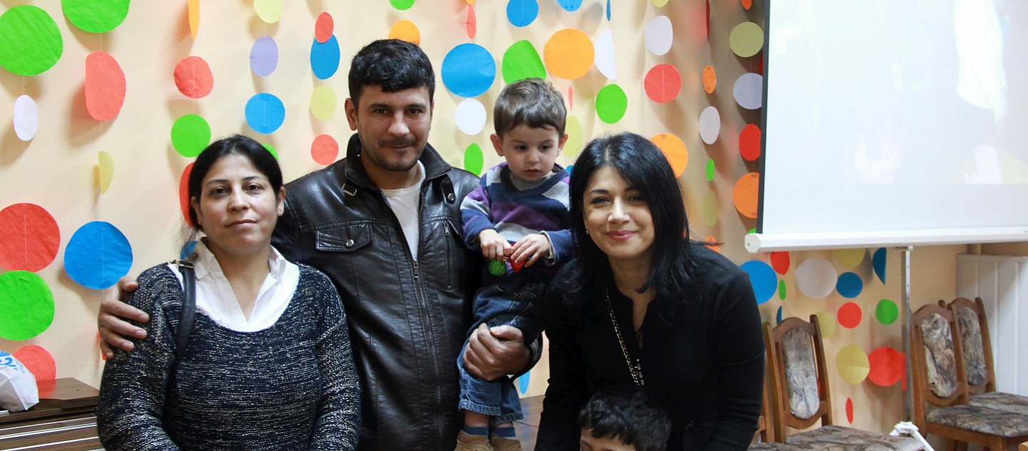 UNHCR Goodwill Ambassador Iskui Abalyan mets a family of resettled refugees in Gomel, Belarus in April 2016. During the mission, she visited the Temporary Accommodation Centre (TAC) to meet refugees from different countries (Ukraine, Syria, Georgia). This photo was taken with a Syrian family at the TAC. They were resettled under the first and the only joint resettlement project of UNHCR and the Ministry of Internal Affairs of Belarus. The family was resettled from Syria to Gomel in February 2015.