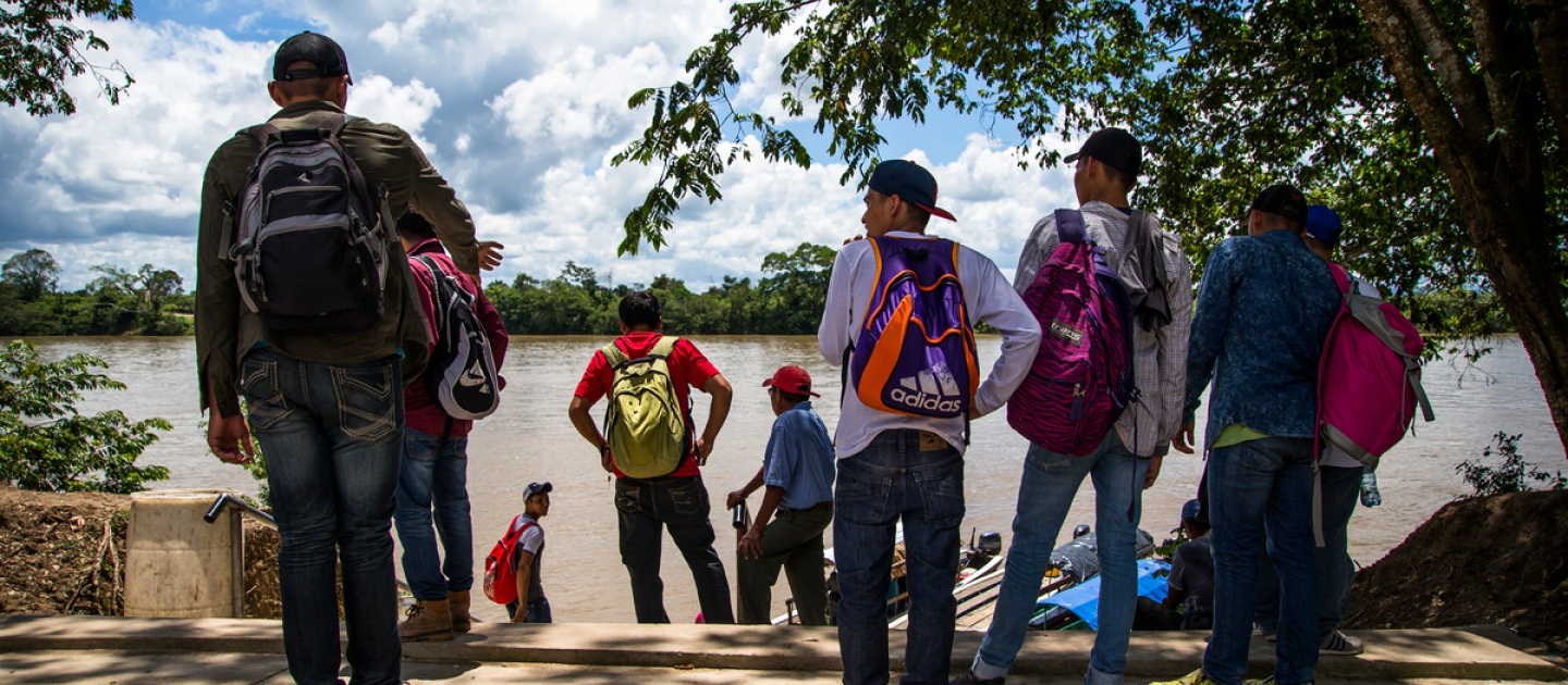 A group of youngsters from Honduras wait by the river for a chance to cross to Mexico.