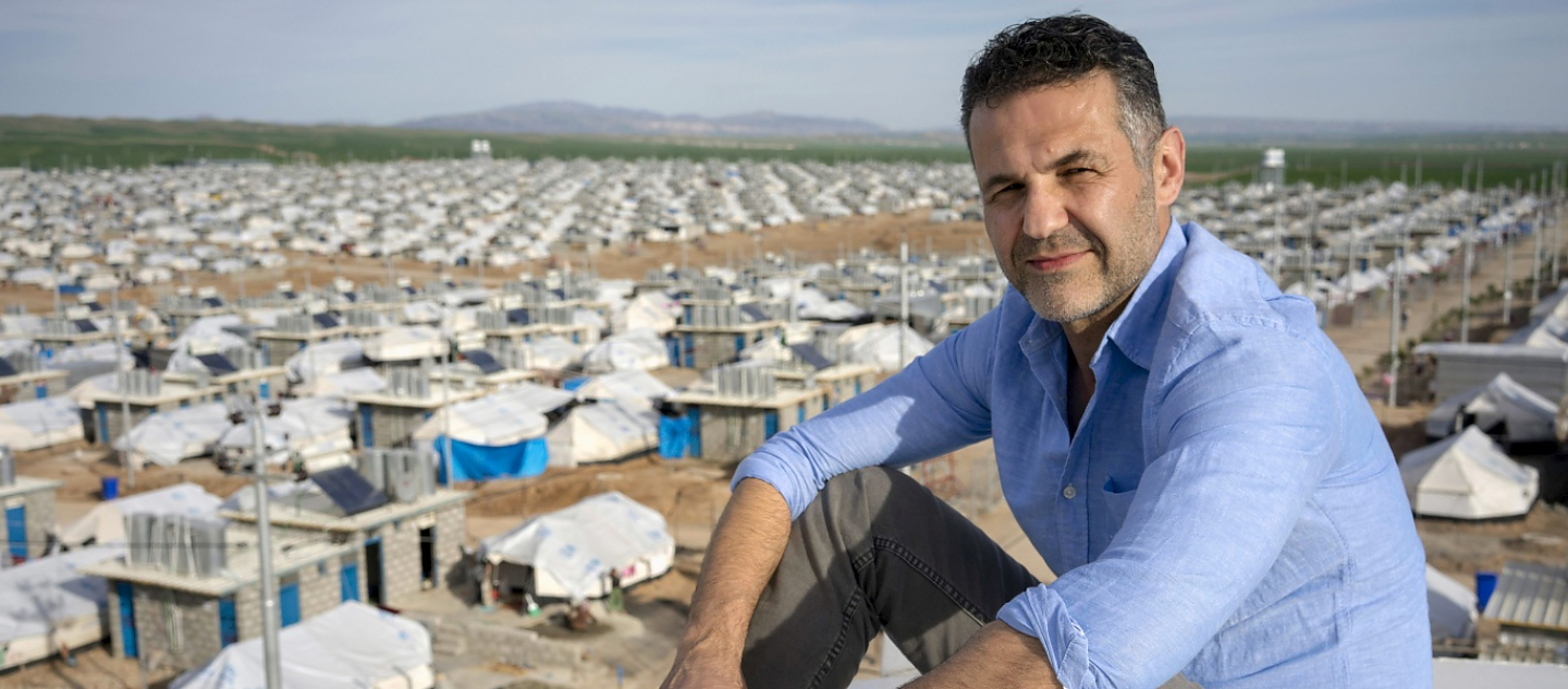 UNHCR Goodwill Ambassador Khaled Hosseini poses for a portrait atop a water tank overlooking Darashakran refugee camp, Iraq