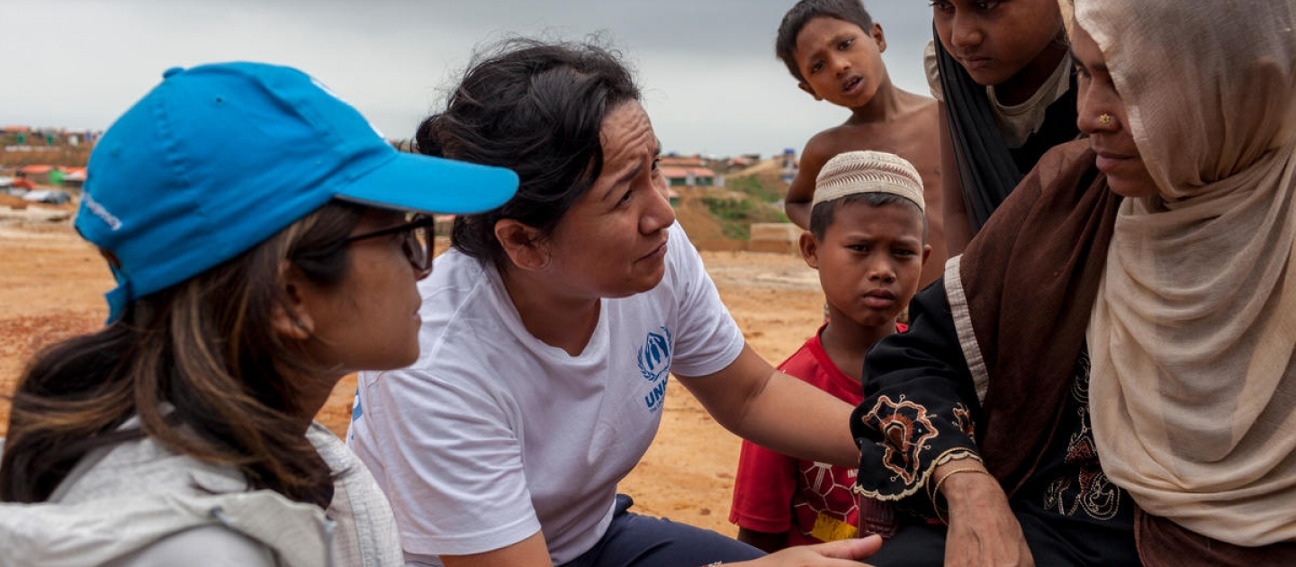 Outside. A women and three children talk with two UNHCR staff.