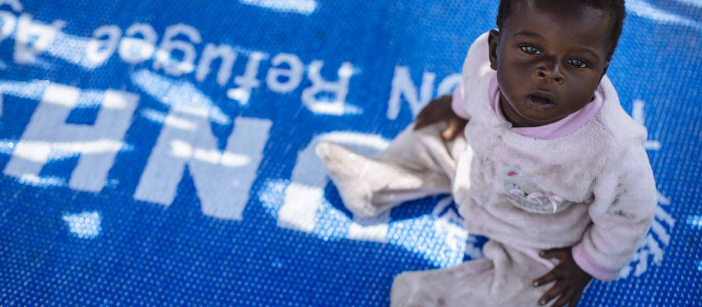 Six-month-old South Sudanese refugee Emma sits on a mat in the shade in Bidibidi refugee settlement, Yumbe District, Northern Region, Uganda.