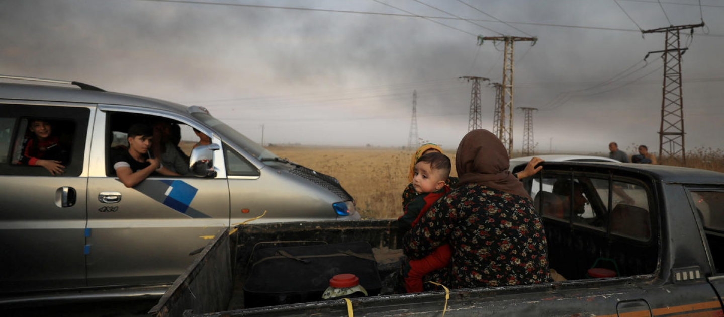 Syria. A woman with a baby sits at a back of a truck as they flee Ras al Ain town
