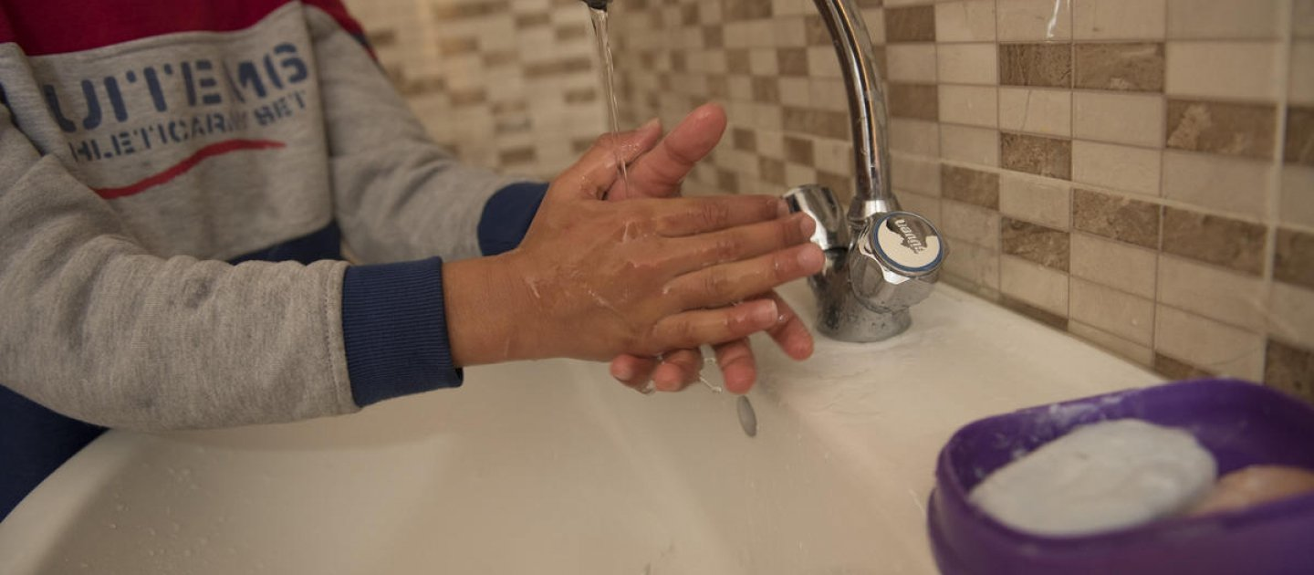 Jordan. Qusai (11) washes his hands in the sink at home