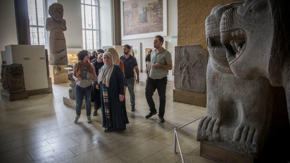 Museum guide Kefah Ali Deeb, 34, leads a group which includes fellow Syrian refugees through Berlin's Ancient Near East of Museum, housed in the Pergamon complex.
