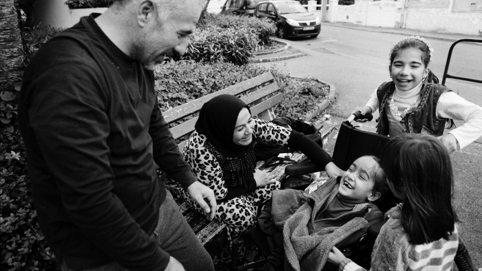 Aya laughs with her family in the garden outside their new flat in Laval, France.