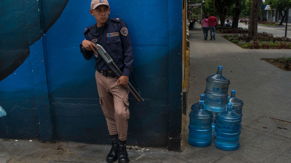 An armed security guard watches over a delivery of water bottles on a street in Guatemala City, where large areas are claimed by extremely violent street gangs. Their crimes range from kidnap and robbery to extortion and murder. The gangs' reach is international.